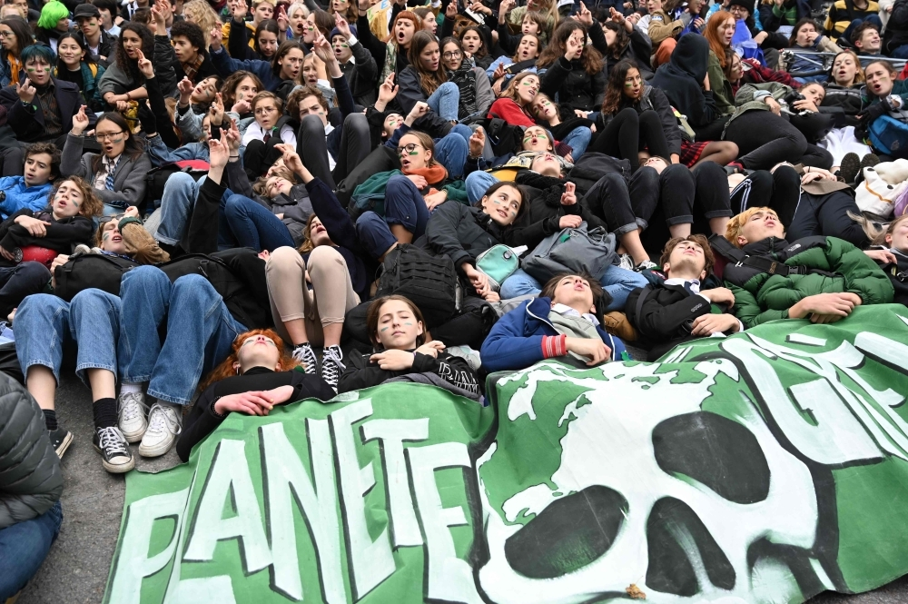 High school students lie on the ground as they protest climate change in front of the Canadian prime minister's campaign office in Montreal on October 18, 2019.  Youth in Montreal and around the world have protested for the environment on Fridays for several months, following the example of Swedish activist Greta Thunberg, who began to protest in August 2018. Youth in Montreal on October 18 called on politicians to take bolder action to stop climate change, ahead of Canada's federal election on October 21. / AFP / Louis BAUDOIN