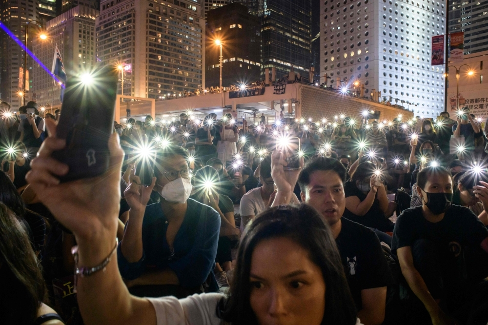 Attendees hold their mobile phones during a rally to show support for pro-democracy protesters in Hong Kong on Saturday. Hong Kong has been battered by more than four months of sometimes violent unrest that have battered the economy, sparked by a now-shelved bill allowing extraditions to the mainland but have since morphed into a movement demanding greater democracy and police accountability. — AFP