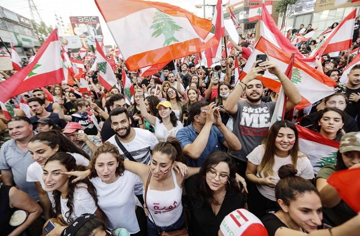 Lebanese demonstrators wave national flags on a highway linking Beirut to north Lebanon, in Zouk Mikael on October 19, 2019, a day after demonstrations swept through the eastern Mediterranean country in protest against dire economic conditions.  Thousands of protesters outraged by corruption and proposed tax hikes burned tyres and blocked major highways in Lebanon on Friday, prompting the premier to give his government partners three days to support a reform drive. / AFP / JOSEPH EID