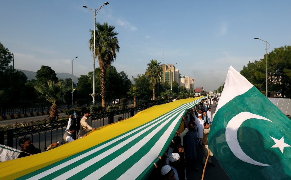 People carry Pakistan's and Azad Kashmir's flag during what they call a freedom march, to express solidarity with the people of Kashmir, in Islamabad, Sunday. —  Reuters