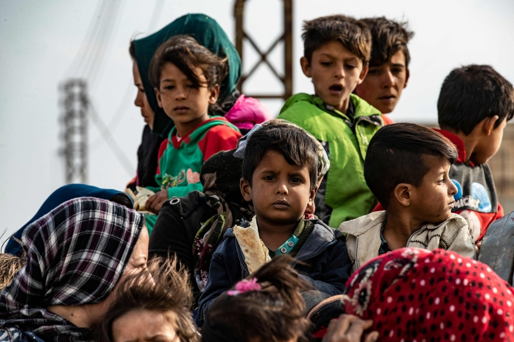 Syrians flee the countryside of the northeastern Syrian town of Ras Al-Ain on the Turkish border, toward the west to the town of Tal Tamr on Saturday. Turkey's President Recep Tayyip Erdogan fired off a fresh warning today to