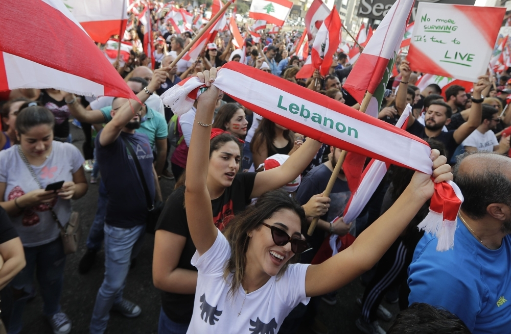 Lebanese demonstrators wave national flags on a highway linking Beirut to north Lebanon, in Zouk Mosbeh as they take part in a rally during the fourth day of demonstrations against tax increases and official corruption, on Sunday. Thousands continued to rally despite calls for calm from politicians and dozens of arrests. The demonstrators are demanding a sweeping overhaul of Lebanon's political system, citing grievances ranging from austerity measures to poor infrastructure. — AFP