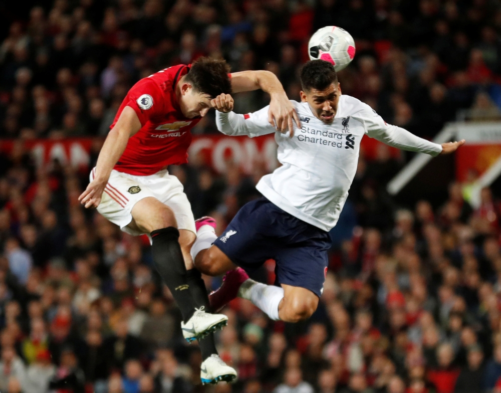Manchester United's Harry Maguire in action with Liverpool's Roberto Firmino at Old Trafford, Manchester, Britain, on Sunday. — Reuters