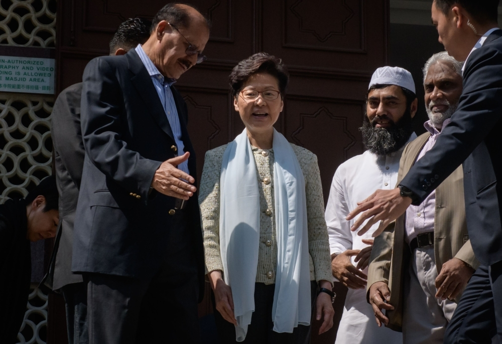Hong Kong's Chief Executive Carrie Lam, center, exits the Kowloon Mosque, or Kowloon Masjid and Islamic Centre, in the Tsim Sha Tsui district in Hong Kong on Monday. — AFP