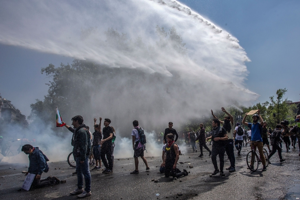 Demonstrators clash with riot police during protests in Santiago on Sunday. — AFP