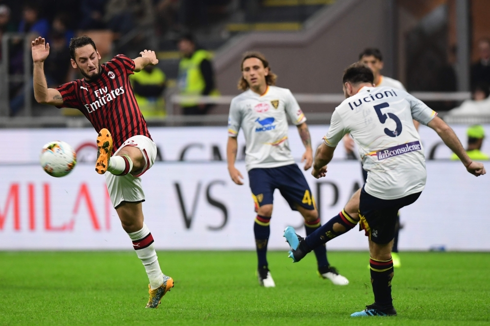 AC Milan's Turkish forward Hakan Calhanoglu (L) attempts to deflect a shot by Lecce's Italian defender Fabio Lucioni (R) during the Italian Serie A football match AC Milan vs Lecce at the San Siro stadium in Milan, on Sunday. — AFP