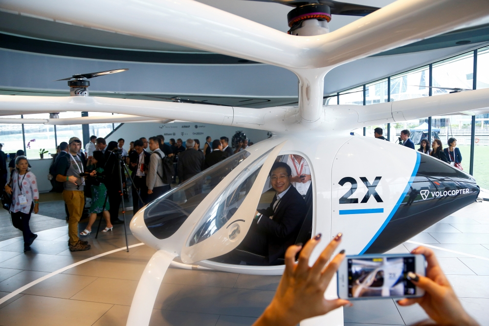 A visitor poses for a photo as he sits inside a Volocopter air taxi model in Singapore on Tuesday. — Reuters