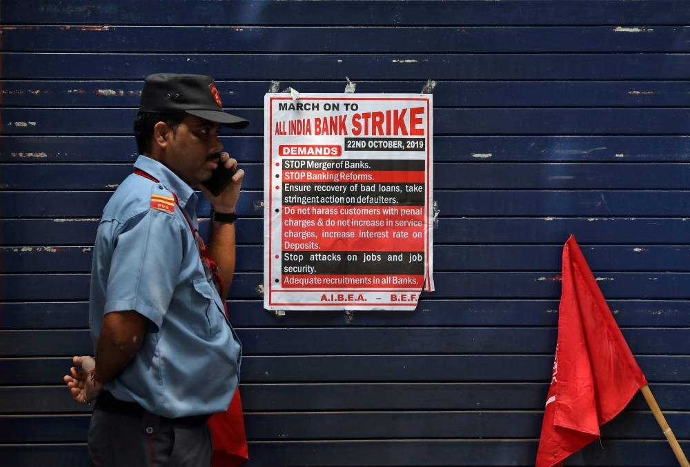 A private security guard speaks in front of a closed Kotak Mahindra Bank branch during a day-long strike against mergers of several state-run banks, in Kolkata, India, on Tuesday. — Reuters