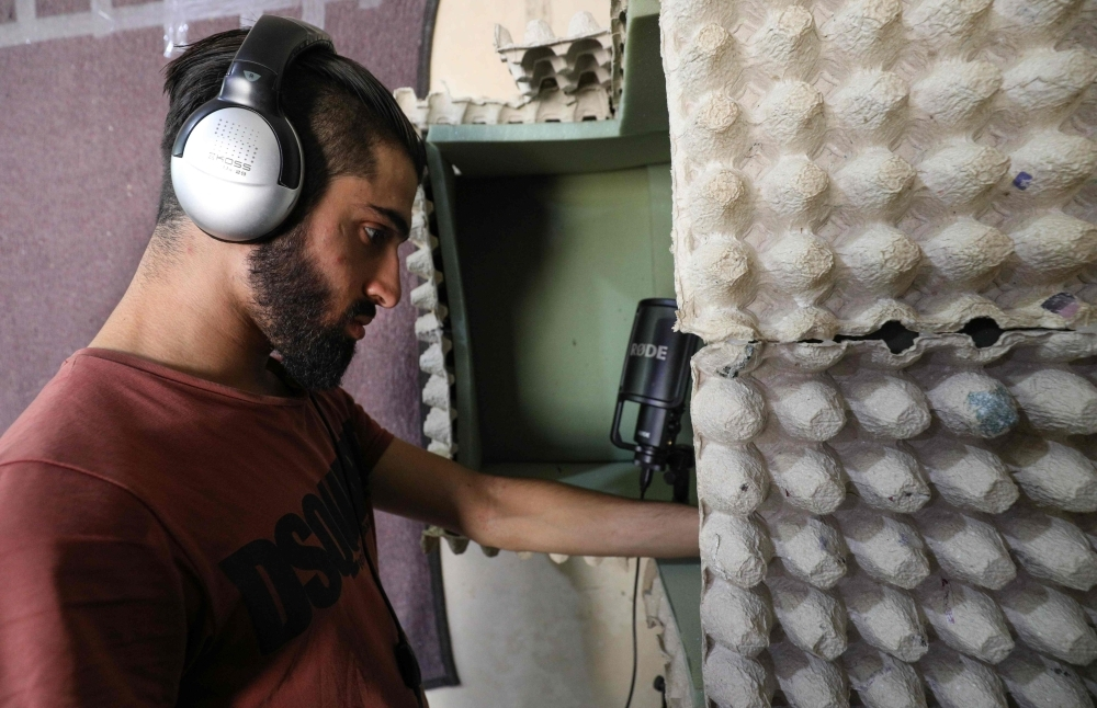 Syrian rapper Amir Al-Muarri works with earphones on, in front of his microphone-equipped booth, padded with soft foam and egg cartons, in his room in the northwestern city of Maaret Al-Numan in the Idlib province in this Sept. 26, 2019 file photo. — AFP
