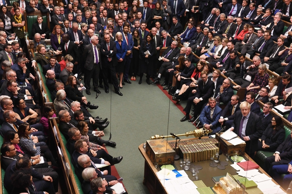 A handout picture released by the UK Parliament shows members of parliament crowding the benches and the aisle listening to Britain's Prime Minister Boris Johnson, right, speak after the results of the vote on the program motion proposing a timetable for the passage of the Brexit Withdrawl Agreement Bill in the House of Commons in London on Tuesday. — AFP