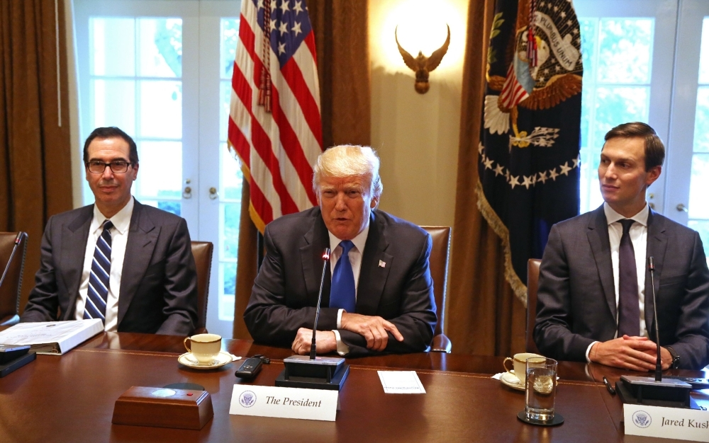 In this file photo taken on July 25, 2017, US President Donald Trump, flanked by his son-in-law Jared Kushner (R) and Treasury Secretary Steven Mnuchin, heads a meeting at the White house in Washington,DC. Mnuchin and presidential adviser Kushner will lead an American delegation to Saudi Arabia's annual financial conference, US media reported on Tuesday. — AFP