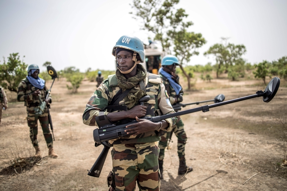 A Senegalese bomb-disposal expert in charge of searching and destroying IEDs holds a detector as he secures the perimeter of a temporary camp in Gani-Do, in central Mali's Dogon region, on July 4, 2019. -AFP