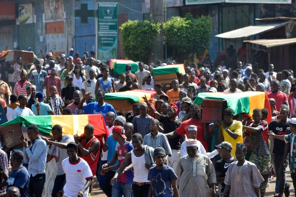 People carry coffins during the funeral after last street protests and unrest that resulted in nine deaths in Conakry, on Monday. -AFP