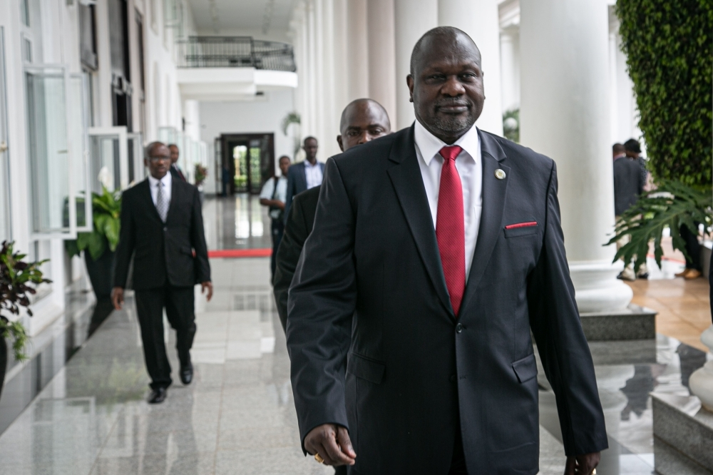 South Sudan's opposition leader Riek Machar, right, arrives for talks on South Sudan's proposed unity government at State House in Entebbe, Uganda, on Thursday. — AFP