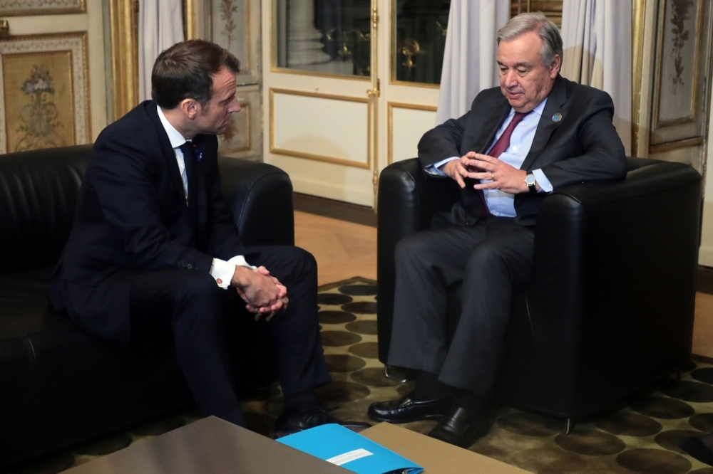 French President Emmanuel Macron, left, attends a meeting with UN Secretary-General Antonio Guterres before a dinner with participants of the Paris Peace Forum, at the Elysee Palace, in Paris, on Monday. — AFP