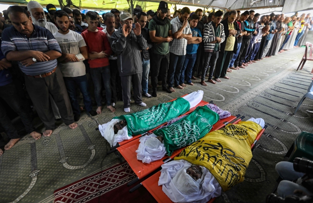 Palestinian mourners pray over three bodies during a funeral in Gaza City on Wednesday. — AFP