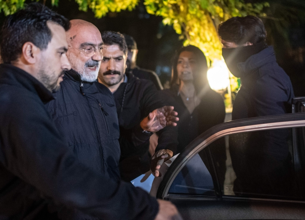 Journalist and writer Ahmet Altan, center, walks with Turkish police as his daughter Senem Altan, right, tries to say him goodbye as he is detained on Tuesday, at Kadikoy neighborhood in Istanbul. — AFP