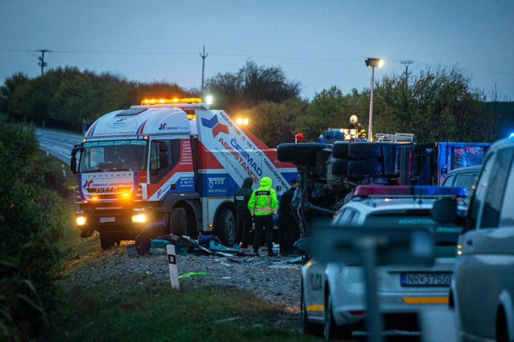 The emergency services work at the scene of collision between a public bus and a truck near the village of Malanta on the outskirts of the city of Nitra, western Slovakia, on Wednesday. — AFP