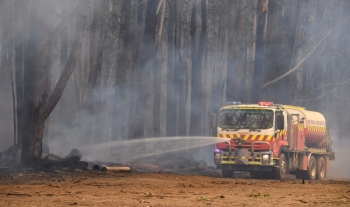 A fire truck hoses down embers after bushfires impacted houses and farmland near the small town of Glenreagh, some 600kms north of Sydney, on Wednesday. -AFP