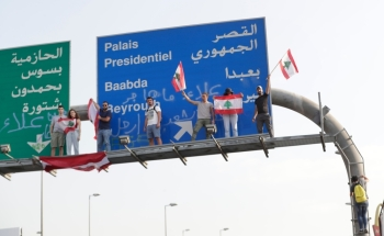Lebanese demonstrators stand on a traffic sign on the road leading to the Presidential Palace in Baabda, on the eastern outskirts of Beirut, on Wednesday. — AFP