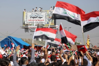 Iraqi protesters chant slogans and wave their country's national flags during ongoing anti-government demonstrations in the southern city of Basra, on Wednesday. — AFP
