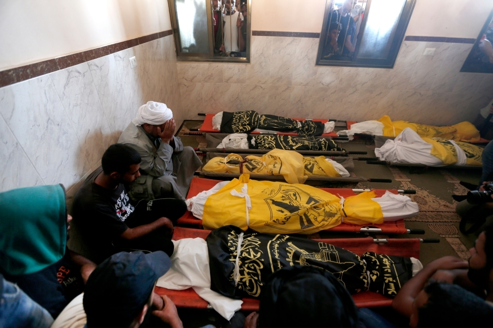 Palestinians mourn over the bodies of members of the same family who were killed overnight in an Israeli air strike in Deir Al-Balah on  Thursday. — AFP
