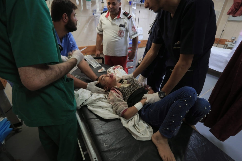 TOPSHOT - Palestinian medical workers tend to a wounded youth, a member of a family where six were killed in an Israeli airstrike, in central Gaza Strip's Deir Al-Balah on Thursday. — AFP
