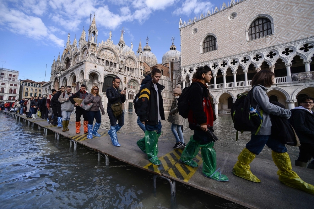 People walk on a footbridge across the flooded St. Mark's Square by St. Mark's Basilica, rear, and the Doge's palace, right, in Venice, Italy, on Thursday. — AFP