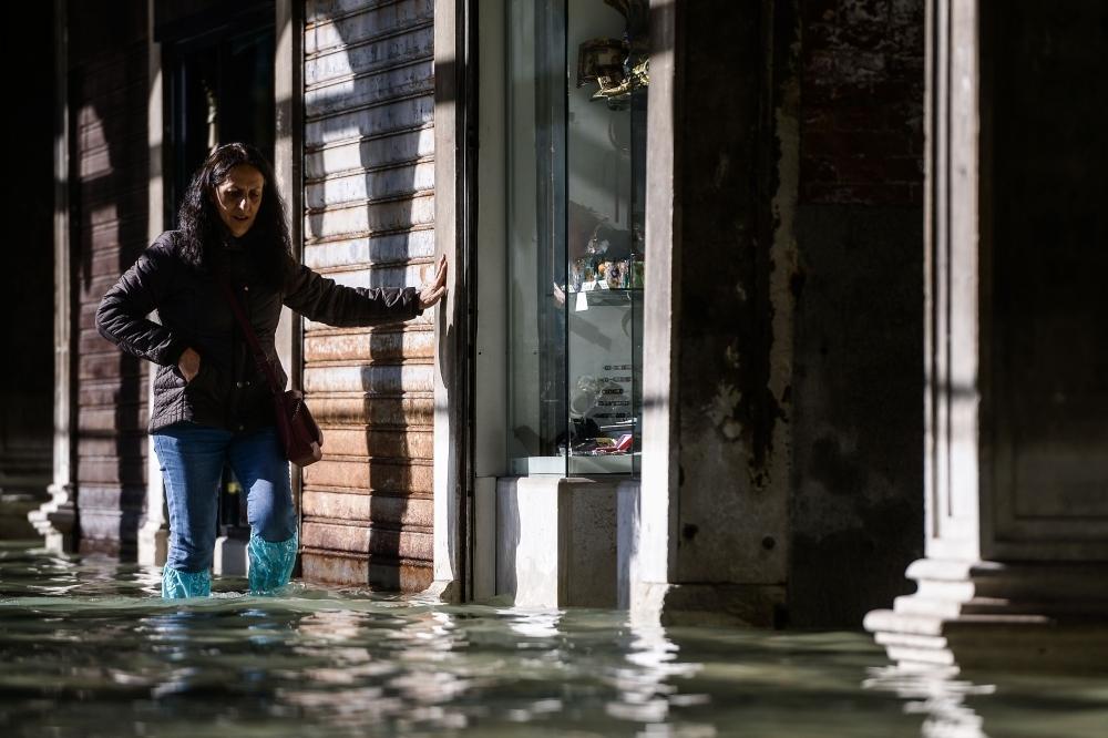 A woman carefully walks across a flooded arcade in Venice, Italy, on Thursday. — AFP