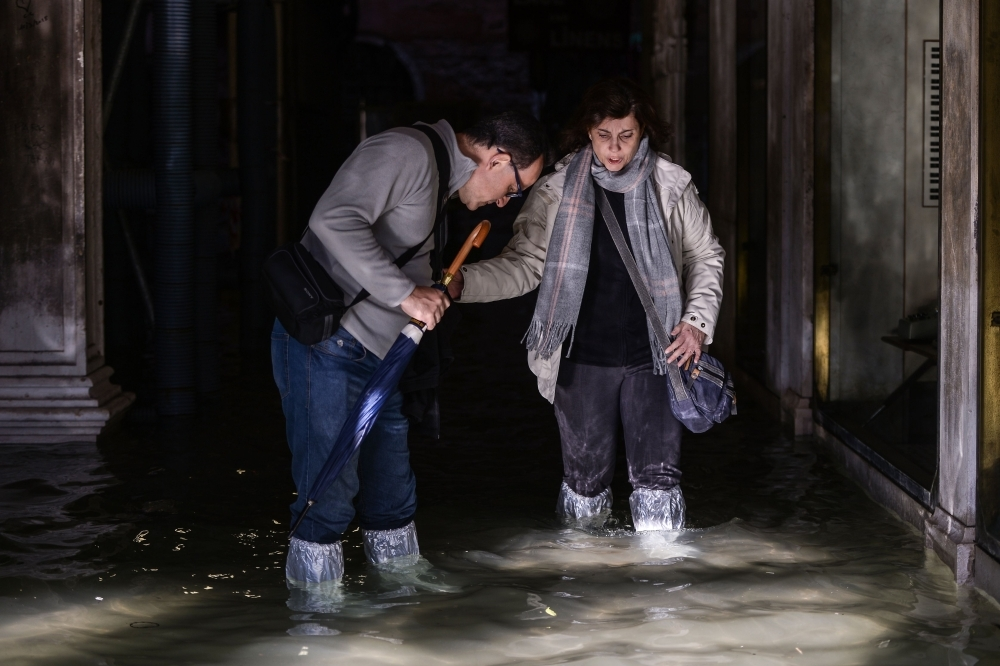 People walk across a flooded arcade in Venice, Italy, on Thursday. — AFP