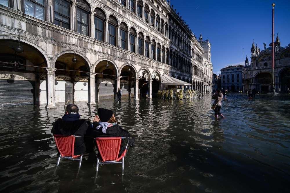 People sit on bistro chairs in the middle of the flooded St. Mark's Square in Venice, Italy, on Thursday. — AFP
