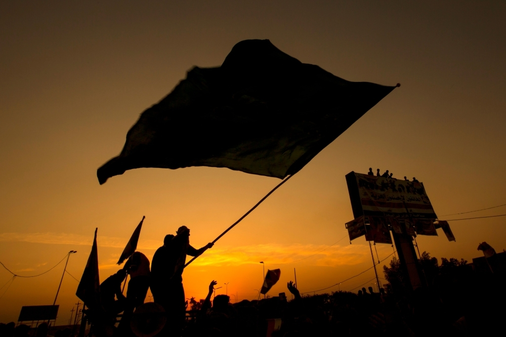 Iraqi protesters wave a flag during a demonstration during ongoing anti-government demonstrations in the southern city of Basra on Wednesday. — AFP