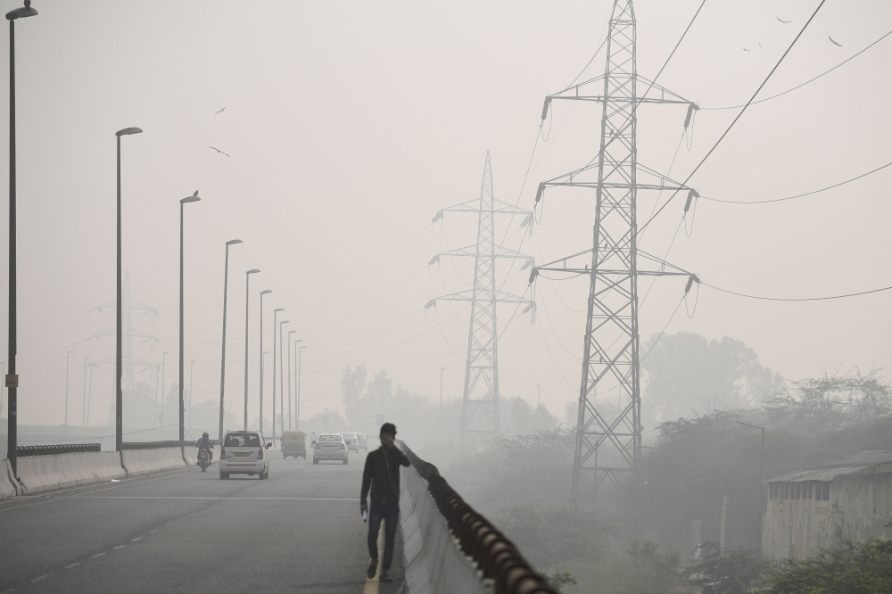 A man walks along a flyover road under heavy smog conditions in New Delhi on Thursday. — AFP