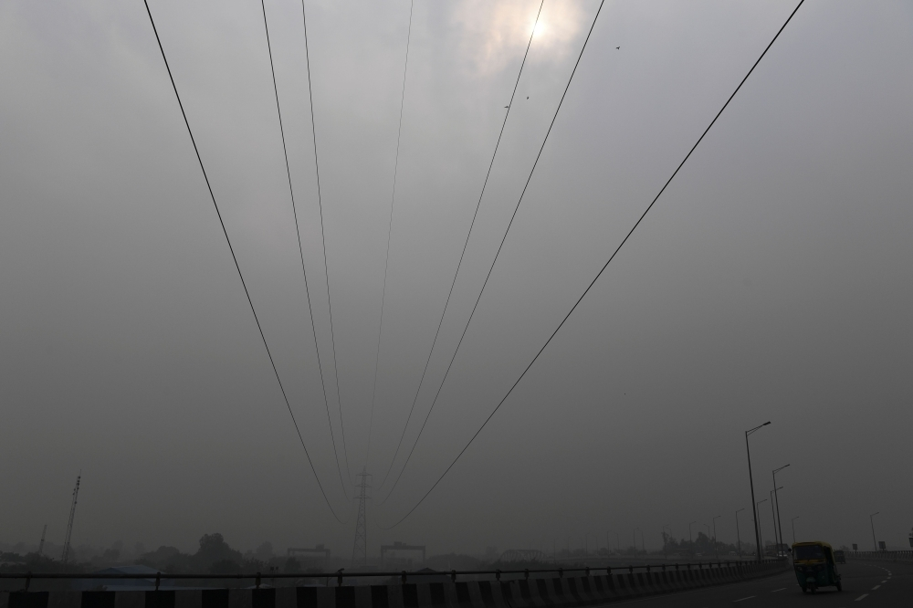 Commuters drive along a motorway under heavy smog conditions in New Delhi on Thursday. — AFP