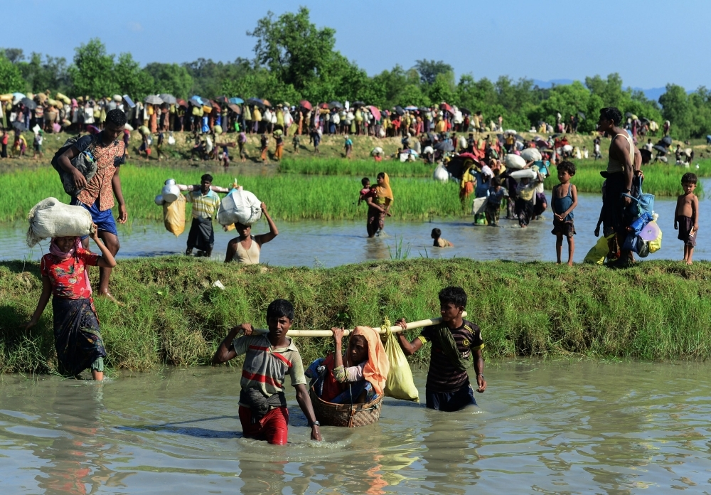 Rohingya refugees carry a woman over a shallow canal after crossing the Naf River as they flee violence in Myanmar to reach Bangladesh in Palongkhali near Ukhia in this Oct. 16, 2017 file photo. — AFP
