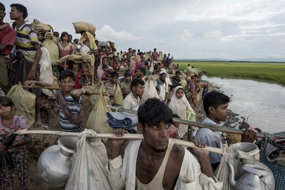 Rohingya refugees walk with their belongings after crossing the Naf river from Myanmar into Bangladesh in Whaikhyang in this Oct. 9, 2017 file photo. — AFP