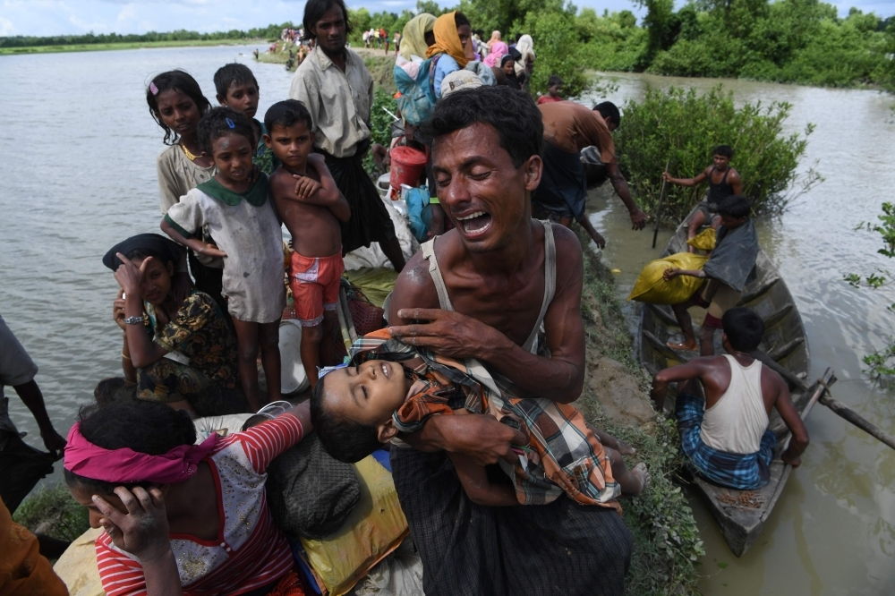A Rohingya refugee reacts while holding his dead son after crossing the Naf river from Myanmar into Bangladesh in Whaikhyang in this Oct. 9, 2017 file photo. — AFP