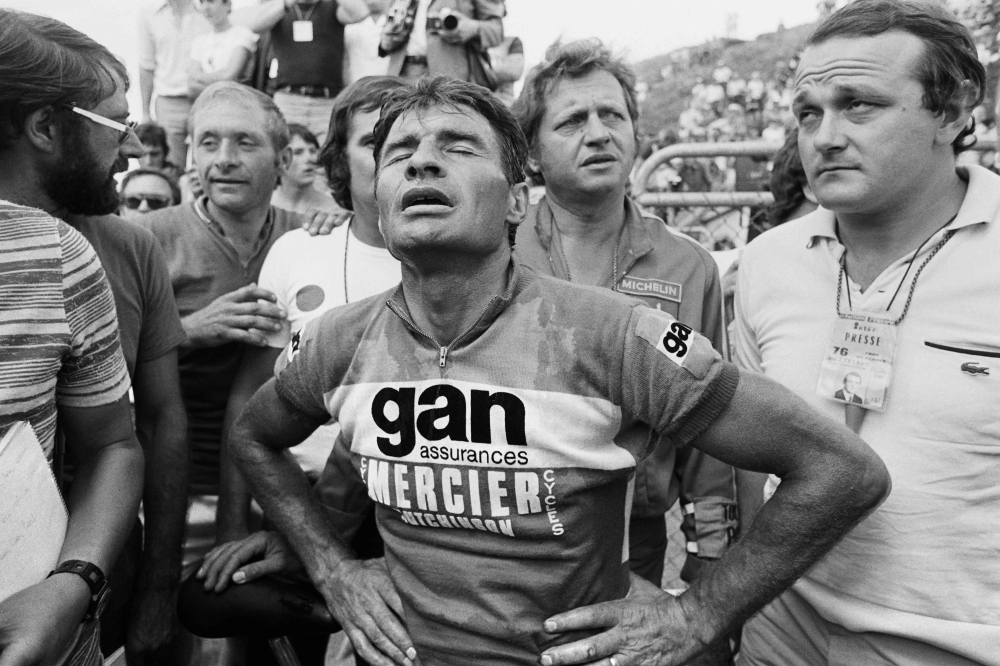 In this file photo taken on July 16, 1976 French Bicycle racer Raymond Poulidor looks exhausted as he arrives third at the 20th stage of the Tour de France, Tulle - Puy de Dôme, flanked by sports reporter Jean-Marie Leblanc. Poulidor died on Nov. 13, 2019 aged 83, his family announced. — AFP