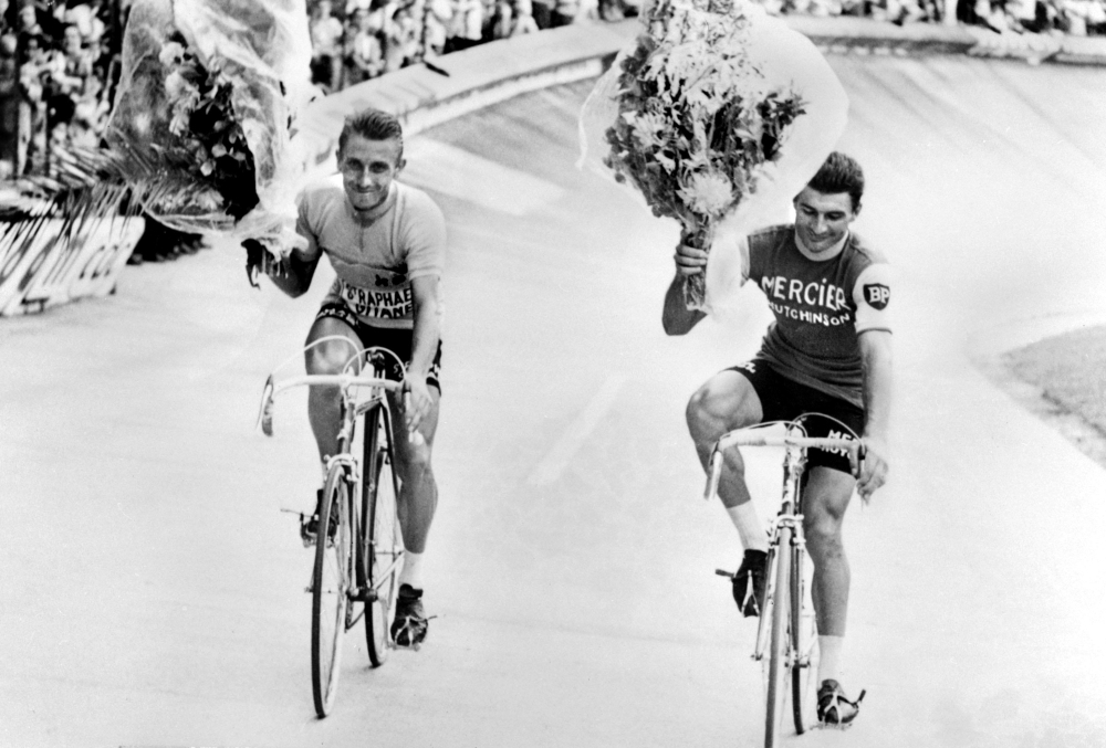 In this file photo taken on July 14, 1964 Frenchman Jacques Anquetil (L), winner of the Tour de France, and his compatriot Raymond Poulidor, second, ride on a victory lap at the Parc des Princes in Paris. Poulidor died on Nov. 13, 2019 aged 83, his family announced. — AFP
