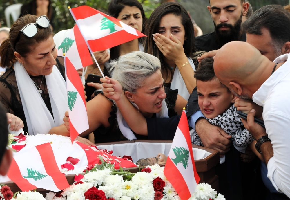 The wife, second left, son, second right, and relatives of slain Lebanese protester Alaa Abu Fakhr mourn over his body during his funeral in his hometown of Chouaifet, southeast of Beirut, on Thursday. — AFP