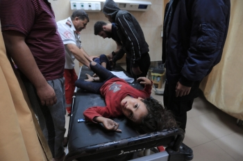 Palestinian medical workers tend to wounded children, members of a family where six were killed in an Israeli air strike, in central Gaza Strip's Deir Al-Balah on Thursday. — AFP