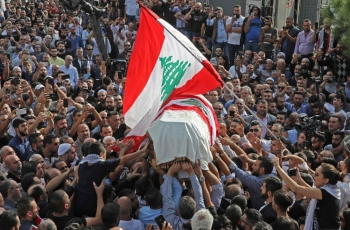 The coffin of slain Lebanese protester Alaa Abu Fakhr, draped in a national flag, is carried  by mourners through the streets of his hometown of Chouaifet, southeast of Beirut, during his funeral procession on Thursday. — AFP
