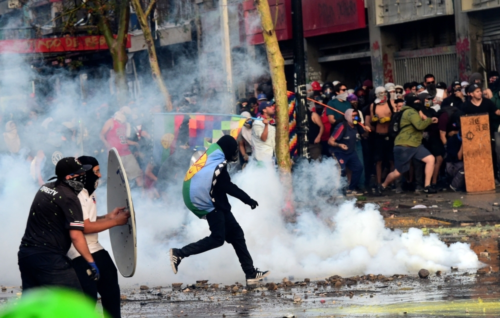 Demonstrators clash with riot police during a protest against the government and to commemorate the first anniversary of the death of Mapuche indigenous leader Camilo Castrillanca, killed in a police operation, in Santiago, on Thursday. The demonstrators are demanding greater social reform from President Sebastian Pinera, who has announced several measures in a bid to appease protesters, including a pledge to change the constitution that dates from the 1973-90 Augusto Pinochet dictatorship. — AFP