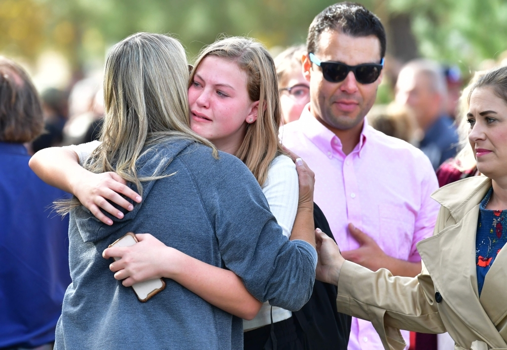Students and parents embrace after being picked up at Central Park, after a shooting at Saugus High School in Santa Clarita, California on Thursday. — AFP
