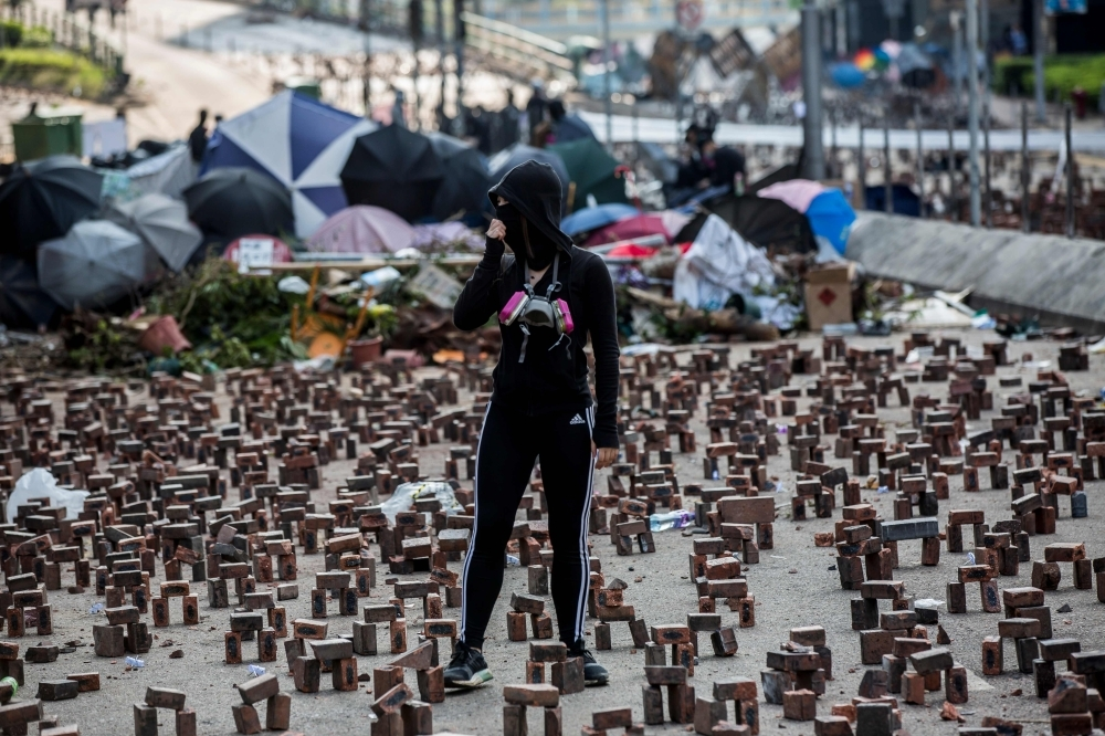 A protester, center, stands among bricks placed on a barricaded street outside The Hong Kong Polytechnic University in Hong Kong on Friday. — AFP