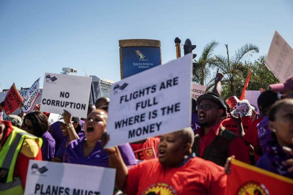 SAA (South African Airways) workers and union members sing and dance during a picket protest outside the O.R. Tambo International Airport in Johannesburg, South Africa, on Friday. The South African airline company has canceled nearly all its domestic, regional and international flights following the strike. — AFP
