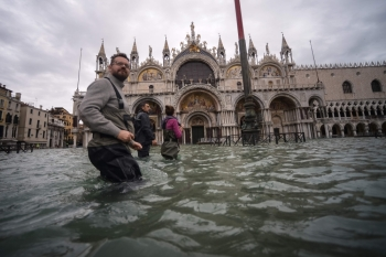People walk across the flooded St. Mark's Square, by St. Mark's Basilica on Friday in Venice, two days after the city suffered its highest tide in 50 years. — AFP