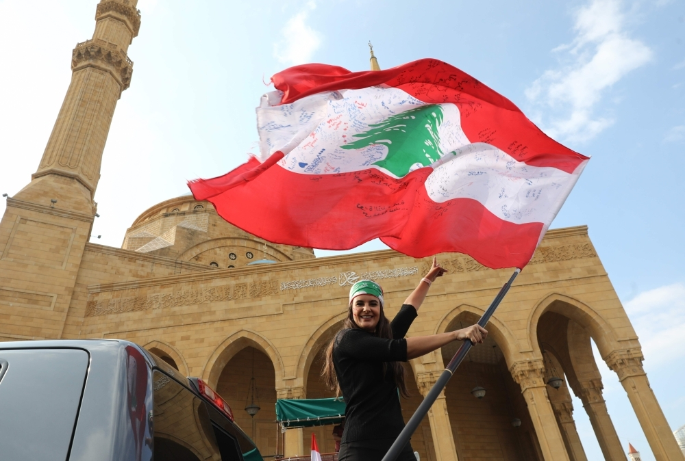 A Lebanese anti-government protester waves the national flag as she prepares to head to the south of Lebanon on a 'revolution' bus from central Beirut on Saturday. -AFP