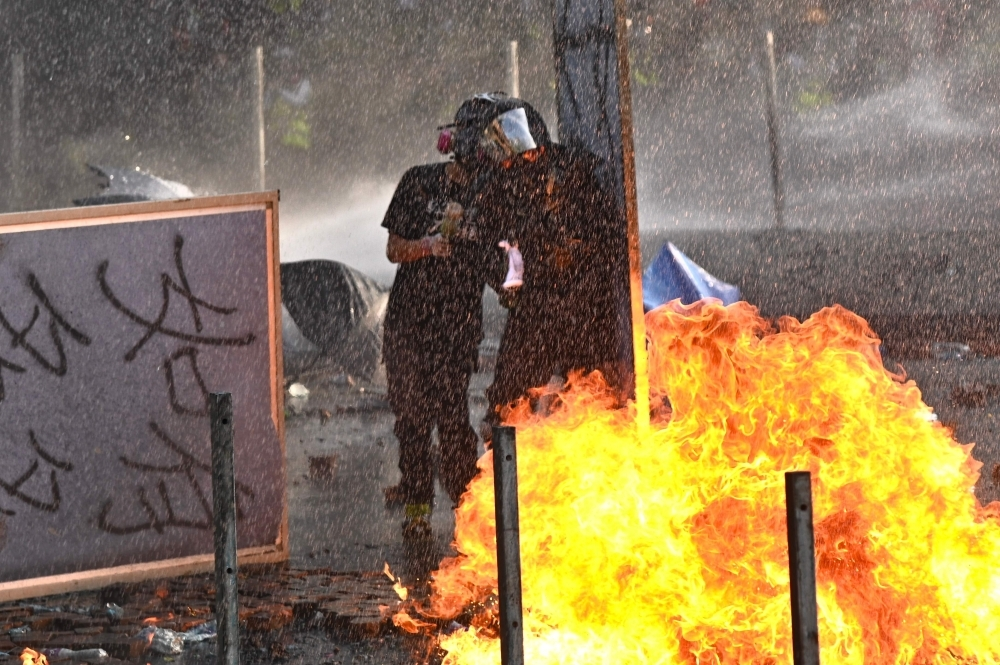Protesters throw Molotov cocktails at the police who use water canon outside the Hong Kong Polytechnic University in Hong Kong on Sunday. -AFP