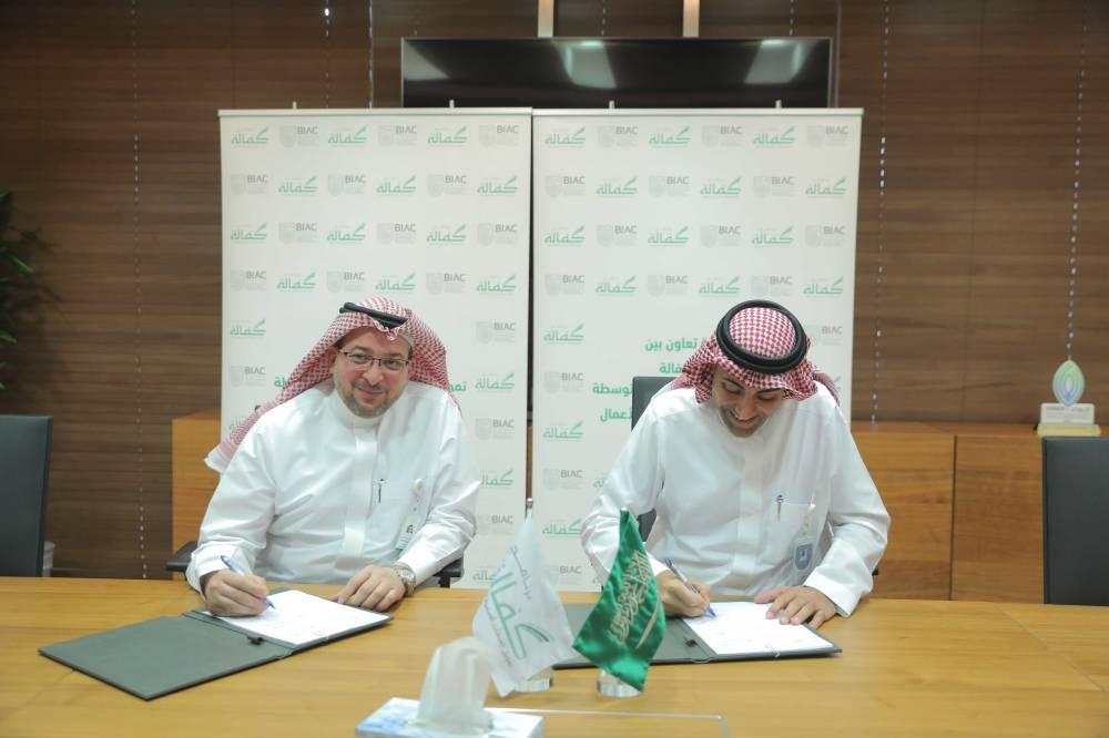 Homam Hashem, General Manager of Kafalah Program; and Nawaf Al Sahhaf, the CEO of BIAC, sign the agreement